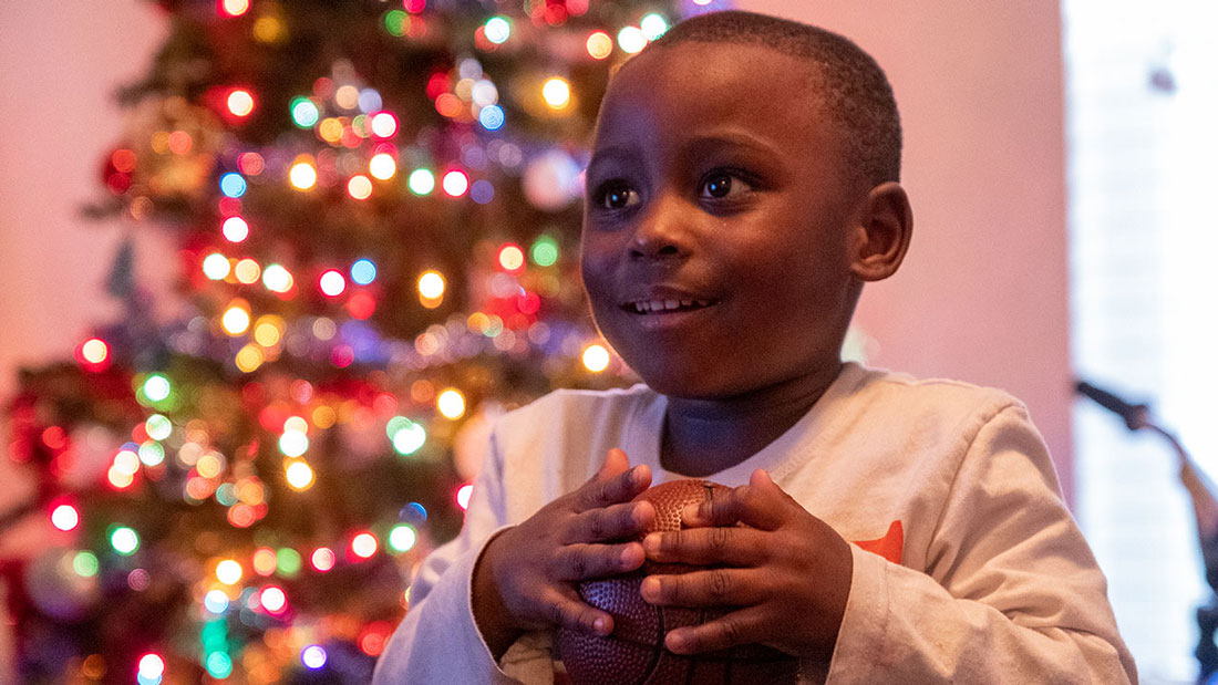 Child stands happily in front of his Christmas Tree with his new basketball.